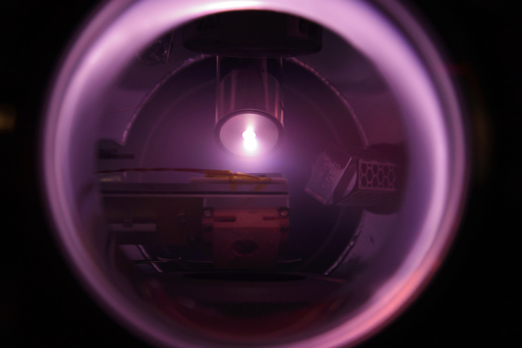purple glow of argon lamp used to clean an ion trap