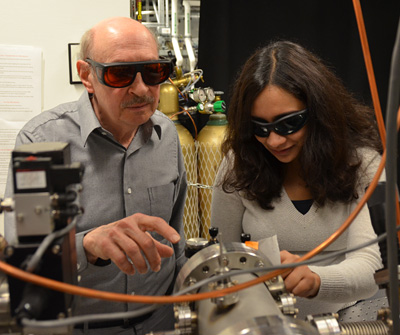 Chemistry professor Stephen Leone and postdoctoral fellow Krupa Ramasesha examine the vacuum chambers of an attosecond laser. (UC Berkeley photo by Robert Sanders)
