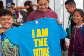 "students hold blue t-shirt with yellow lettering reading ""I am the future"""