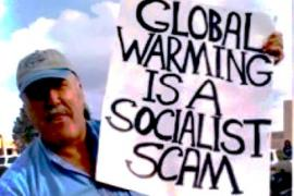 "Man holding sign reading ""Global Warming is a Socialist Scam"""