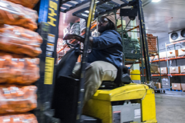 Forklift driver in food warehouse.