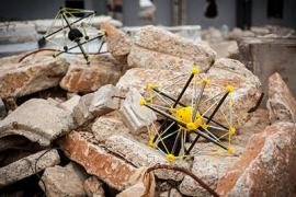 A pair of yellow, buckyball-shaped robots sit on a pile of rubble