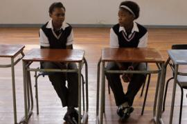 Two South African teen girls sit at desks in a classroom, wearing uniforms
