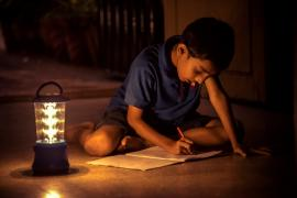 A boy studies by a solar lamp