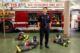 "A photo of Maiko Bristow, a women firefighter with the San Francisco Fire Department. Maiko is wearing a black uniform and her turn out gear sits on the ground around her. Behind her is a fire truck with the words ""San Francisco Fire"""