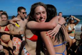 Two spring revelers hug on Pompano Beach in Florida.