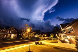 Powerful lightning storm front passes over residential houses