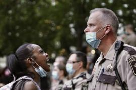 a black woman with a mask at her chin yells at a white male police officer wearing a mask and staring into the distance