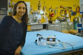 Associate professor Grace O'Connell stands next to a ventilator, which is lying on a table in her lab, that she created from a used sleep apnea machine