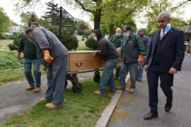 a man in a suit walks along with a wooden casket being rolled by workers in masks