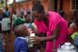 School worker gives a de-worming pill to a young student at a school in Western Kenya