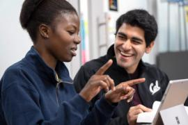 two Berkeley students in animated discussion at a laptop