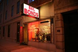 Storefront of a bail bond office on an urban street, with neon lights