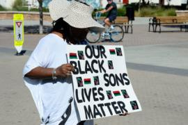 "A Black woman stands in the street, wearing a large hat that obscures her face. She holds a sign that says ""Our Black sons lives matter."""