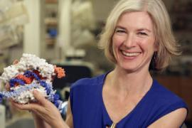 Jennifer Doudna smiles and holds a model of CRISPR-Cas9