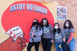 "four people pose by a mural that reads ""Estoy votando"""