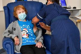 a woman wearing a mask sits in a blue armchair and gets a shot in her arm