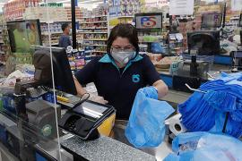 A retail checkout clerk, masked against coronavirus infection, puts purchases into blue plastic bags