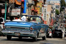 A classic convertible automobile, full of people, driving down a street in San Francisco's Chinatown district