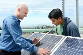Eric Brewer and graduate student inspect solar panel.