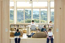 Chartwell School students read and relax in a library/stage/study area.