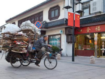 man riding bike in China carrying cardboard