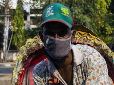 A rickshaw driver in Dhaka, Bangladesh, wears a mask to protect against transmission of the COVID-19 virus.